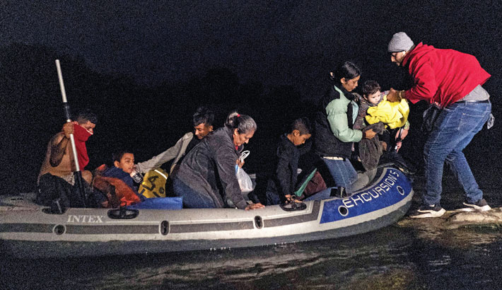 Asylum-seeking migrants' families disembark from an inflatable raft after crossing