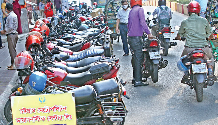 Motorcycles are parked illegally on a road at Golpahar in Chattogram city