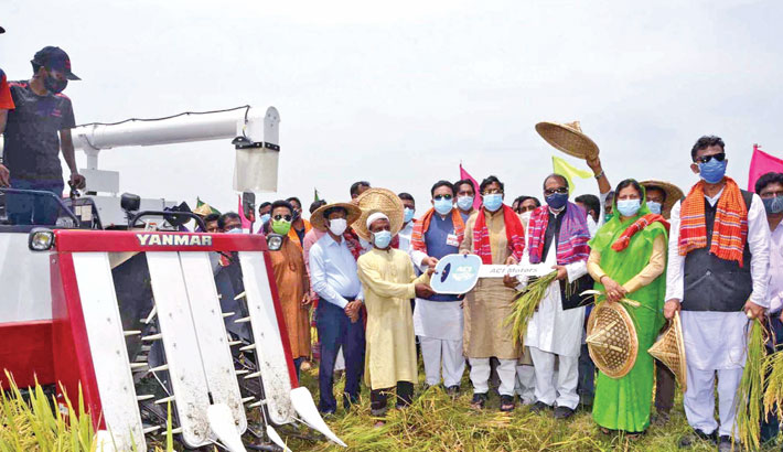 A combine harvester and reaper machine to a farmer at a Boro Paddy Harvesting Festival