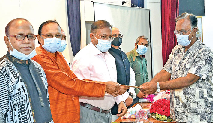Hands over a cheque of Bangladesh Journalists Welfare Trust to a journalist at a cheque distribution programme