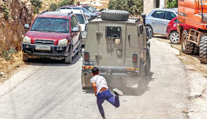 A Palestinian youth throws stones at an Israeli military armoured vehicle