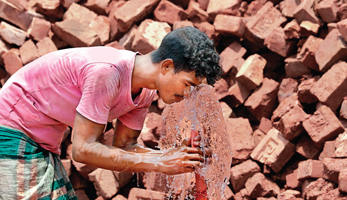 A day labourer washes his face with water in order to cool himself off amid the scorching heat