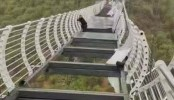 China: Man left dangling from bridge after glass breaks