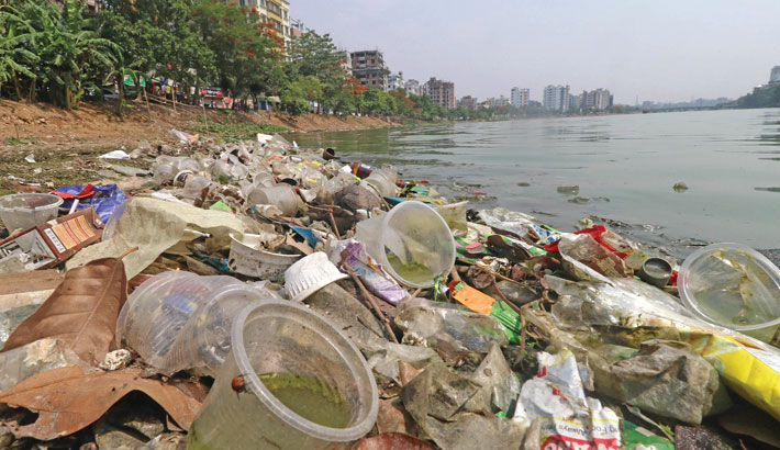 Waste, including plastic bottles and polythene bags, floats in the Hatirjheel Lake of the capital