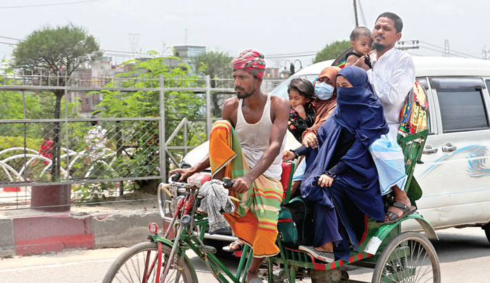A rickshaw-puller who has no face mask is carrying five passengers