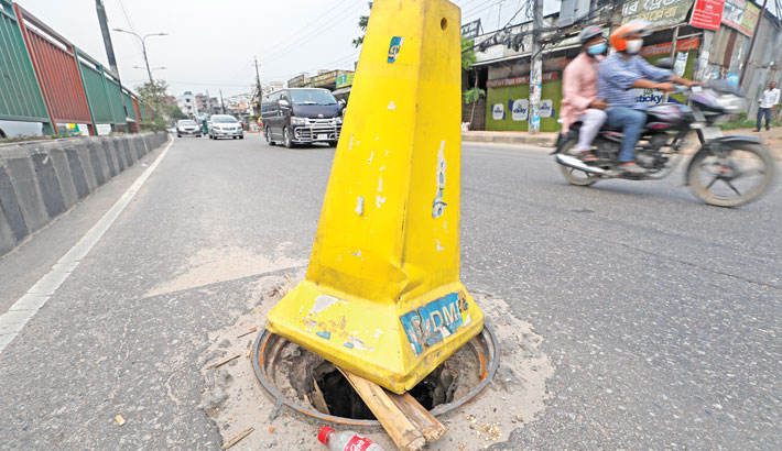 A traffic cone placed by a Good Samaritan warns of a sewer opening