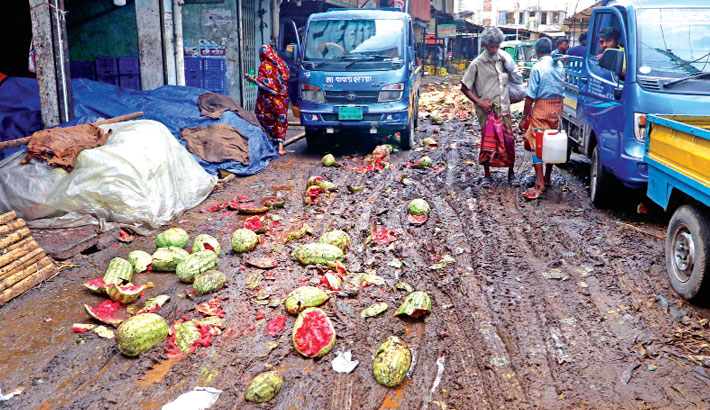 Traders dump rotten fruits indiscriminately on a busy road leading