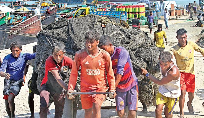 Fishermen wrap up their fishing nets to deposit in owners' godowns as a 65-day ban on fishing