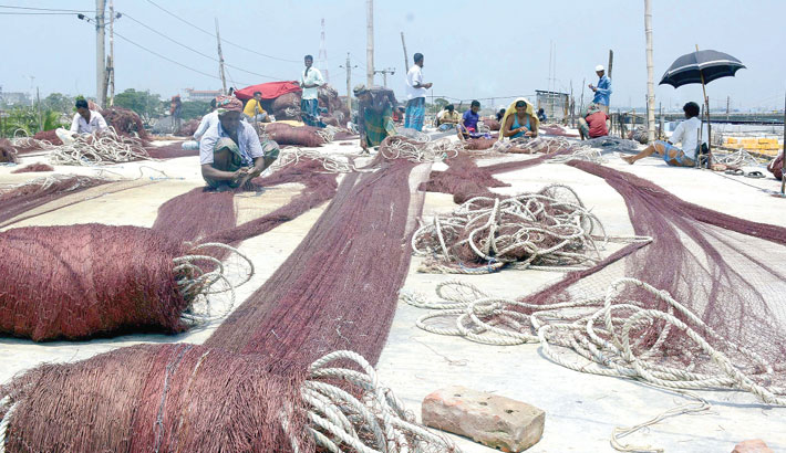 Fishermen are busy repairing fishing nets at Fisheryghat area in Chattogram