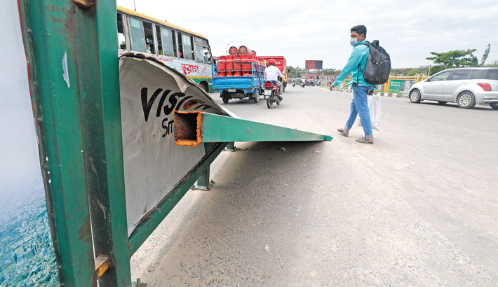 An iron road divider lies damaged on a busy road in the capital's Kuril Biswa Road area