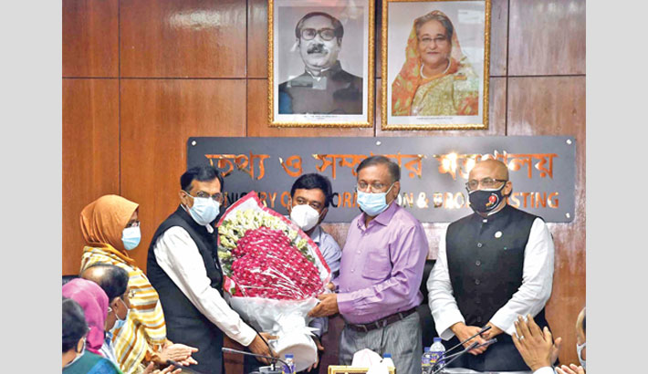 Hands over a bouquet to outgoing secretary of the ministry Khaja Miah at a farewell ceremony
