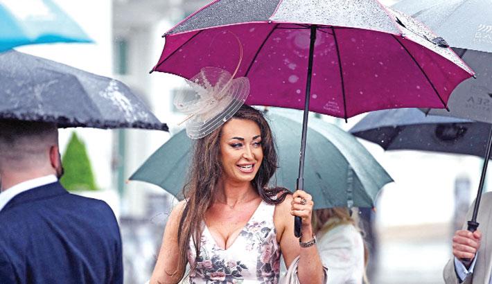 Racegoers shelter under umbrellas in London