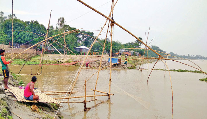 Two boys are catching fish with traditional fishing nets