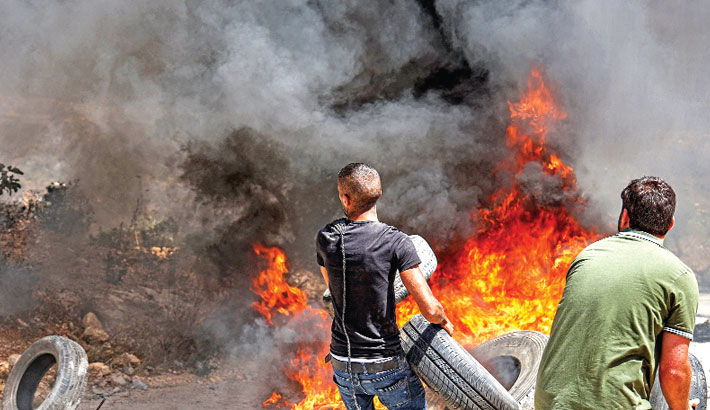 Palestinian protesters set tires aflame during clashes with Israeli security forces following