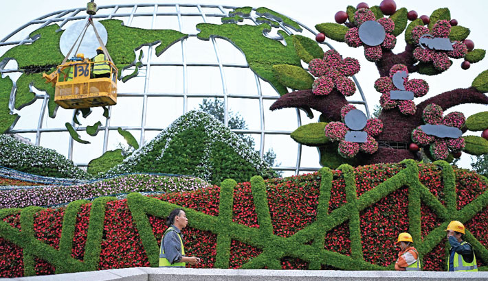 Workers are seen decorating a flower display for along a street in Beijing on Saturday