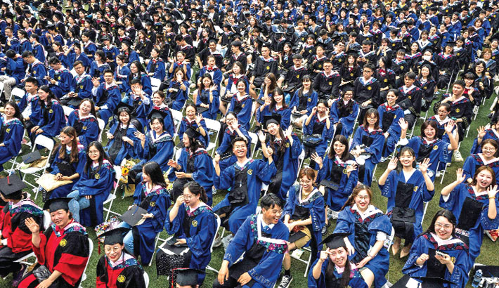 This photo taken on Sunday shows nearly 9000 graduates, including more than 2000 students who could not attend the graduation ceremony last year due to the Covid-19 outbreak, attending a graduation ceremony at Central China Normal University in Wuhan, in China's central Hubei province.     – AFP PHOTO