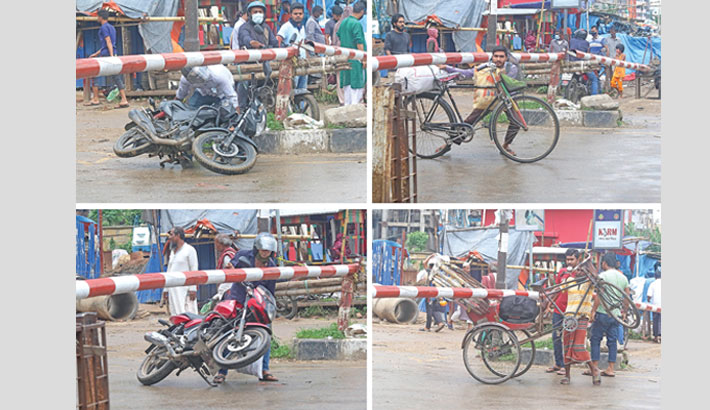 In the photo taken from a level crossing in the capital's Tejgaon area on Wednesday, two motorcyclists, a cyclist and a rickshaw-puller are seen crossing rail tracks defying the boom barrier and paying no heed to the impending danger from the approaching train.—MD NASIR UDDIN