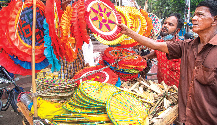 A man sells colourful hand fans on a street at Sathmatha intersection in Bogura district town amid the scorching heat. The photo was taken on Friday.— Monirul Islam Maruf