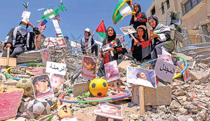 Palestinians wave their national flag behind images of victims amidst the rubble of buildings destroyed by last month's Israeli bombardment of the Gaza Strip, in Khan Yunis, in the southern Gaza Strip on Saturday. – AFP PHOTO