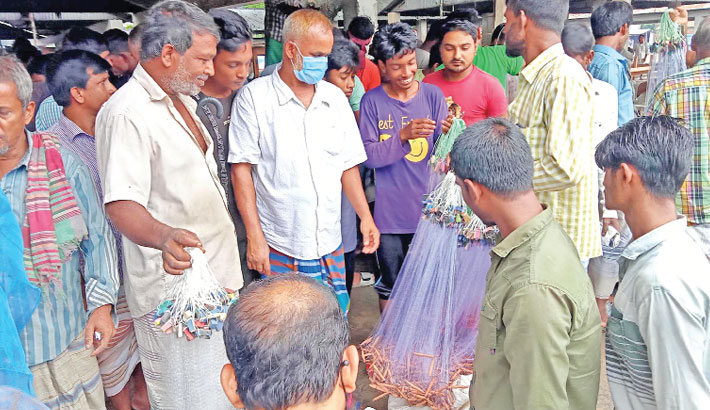 Buyers gather at a local market to buy fishing nets without maintaining health guidelines amid the pandemic. Demand for fishing nets has increased as rainy season has set in.  The photo was taken from Dashuria in Ishwardi upazila of Pabna district on Saturday. — PBA Photo