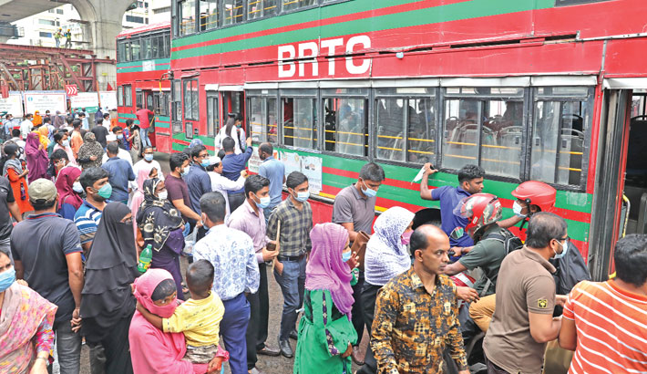 Passengers are scrambling to get on a bus at Shahbagh intersection in the capital on Sunday defying government instructions to maintain social distancing amid the worsening coronavirus situation.—SUN PHOTO