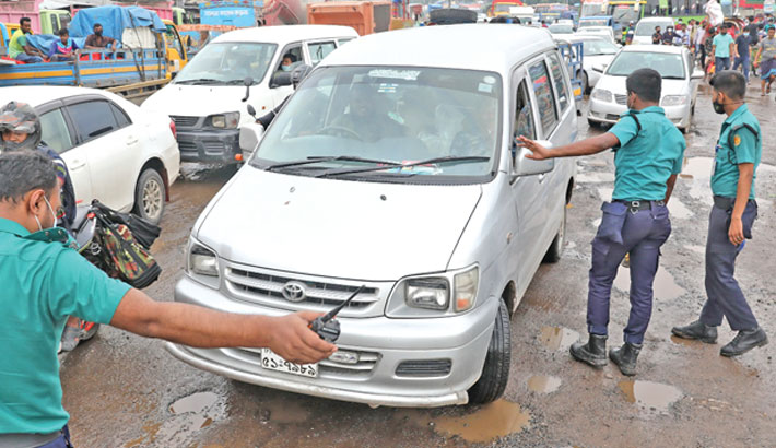 Police stop vehicles especially private ones, at Aminbazar, one of the entry ways of Dhaka city, on Dhaka-Aricha highway on Tuesday, and ask reasons behind their commute as strict restrictions have been enforced in some districts in an effort to beat the deadly coronavirus. —SUN photo