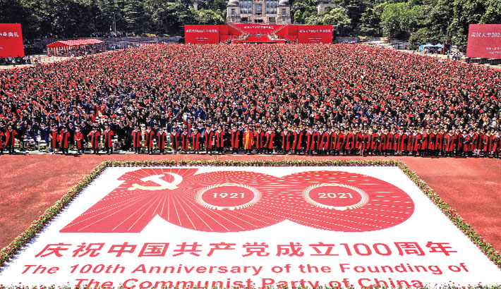 Graduates of Wuhan University pose for photos in front of an image commemorating the 100th anniversary of the Chinese Communist Party as they attend the graduation ceremony in Wuhan, in China's central Hubei province on Wednesday. – AFP PHOTO