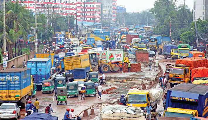 Vehicles are moving at a snail's pace on a portion of Dhaka-Mymensingh highway from Abdullahpur in the capital to Gazipur as rain has created potholes, causing sufferings for commuters. The photo was taken from Tongi area of Gazipur city on Wednesday. – Reaz Ahmed Sumon