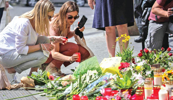 Two women place a candle at a makeshift memorial of flowers and candles in tribute to the victims of a deadly attack in the city center of Wuerzburg, southern Germany, on Saturday. —AFP PHOTO
