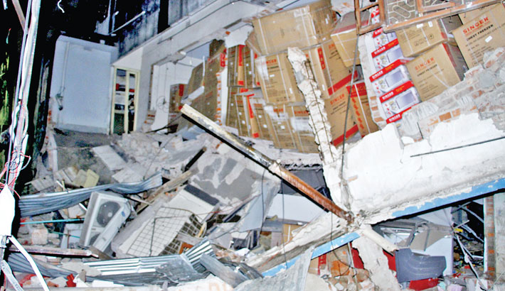 Flying debris from an explosion that takes place at a building at Moghbazar in the capital on Sunday evening lands on a road. The incident leaves at least six people dead and 50 others injured.—sun photo