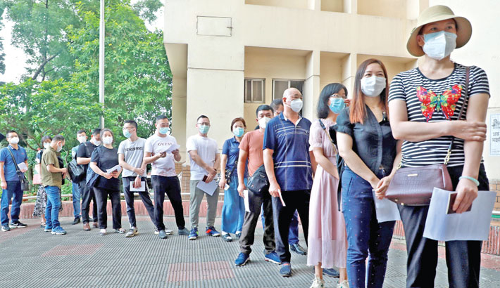 Chinese citizens living in Bangladesh wait in a queue at Mugda Medical College Hospital in the capital on Tuesday to receive the second dose of Covid-19 vaccine. —SUN photo
