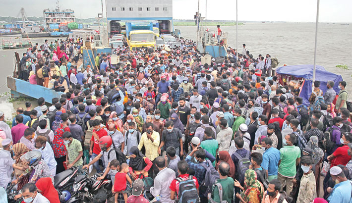 People are cramming into a ferry at Shimulia Ghat in Munshiganj on Wednesday to cross the Padma River amid risk of getting infected by coronavirus. A large number of people left the capital ahead of a seven-day countrywide strict lockdown beginning today.—Reaz Ahmed Sumon