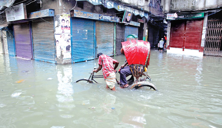 A rickshaw-puller struggles to move through knee-deep water on a road submerged by rainwater in Old Dhaka's Bongshal area on Friday.—sun photo