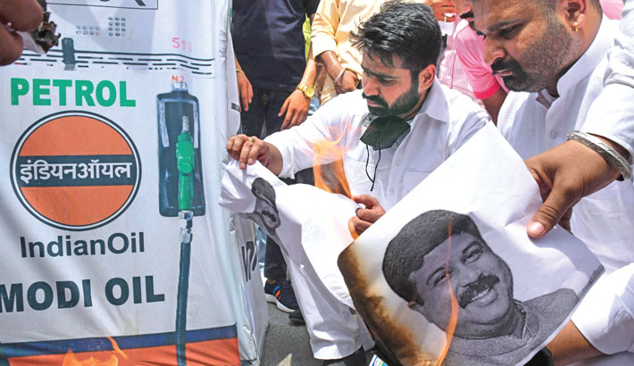 Activists of the National Students' Union of India (NSUI) shout slogans and burn pictures of Petroleum Minister Dharmendra Pradhan during a protest against the hike in petrol and diesel prices, in Amritsar on Friday. – AFP Photo