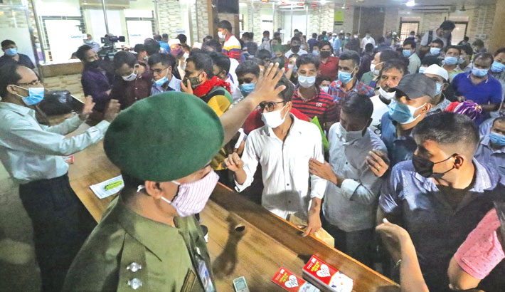 Officials of the Expatriates' Welfare Ministry try to calm outbound migrant workers after the ministry fails to register them (migrant workers) for Covid-19 vaccine through app on the ministry premises in the capital on Friday. —Md Nasir Uddin