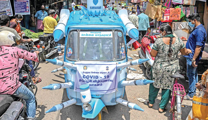 A municipal worker drives an auto-rickshaw decorated with mock syringes through the streets to boost awareness amid people on the importance of coronavirus vaccination in Chennai on Saturday.    AFP PHOTO