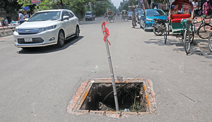 A piece of red cloth tied with a bamboo stick warns of a sewer opening, the lid of which has been missing for long, at Road-15 of Dhanmondi in the capital, disrupting the vehicular movement and posing risk of accident. The photo was taken on Monday.—Kamrul Islam Ratan