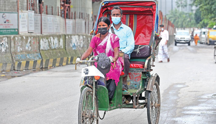 Parvin lost her job of domestic help when coronavirus started spreading in the country. However, instead of seeking help from others, the spirited woman started pulling a rickshaw to eke out a living. The photo was taken from Shahbagh area of the capital on Tuesday. – Reaz Ahmed Sumon