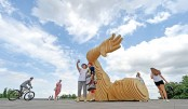 Passers-by pose in front of Merman Art, a half-sunk wooden statue of a swimmer, in Kiev on Tuesday. Merman Art has been created by Merman team, a group of artists from Ukraine, for the US Burning Man festival. – AFP PHOTO
