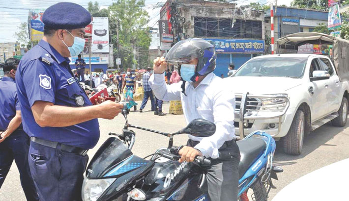 Traffic police halt a motorcyclist to ask for reasons for being out on the street at a check post in Bogura district town on Wednesday during the ongoing lockdown to imposed to check the spread of coronavirus.— Star Mail