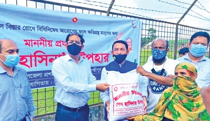 On behalf of Prime Minister Sheikh Hasina, Lawmaker from Lakshmipur-2 constituency Nurunnabi Chawdhury Nayan and Deputy Commissioner of Lakshmipur Md Anwar Hossain Akand distributes relief materials among lockdown-hit workless people in Lakshmipur Stadium in the district town on Thursday.— Sun Photo