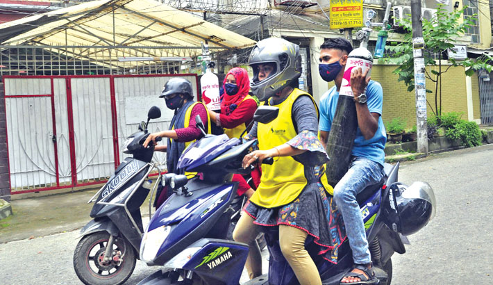 Volunteers carry oxygen cylinders to deliver those to the houses of critically ill Covid-19 patients in the city for free. The snap was taken from Mohammadpur area on Friday. —SUN photo