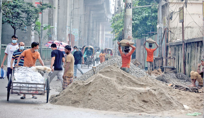 Construction materials pile up on a road in the city's Banglamotor area, causing problems for pedestrians and commuters. The photo was taken on Saturday. —SUN photo