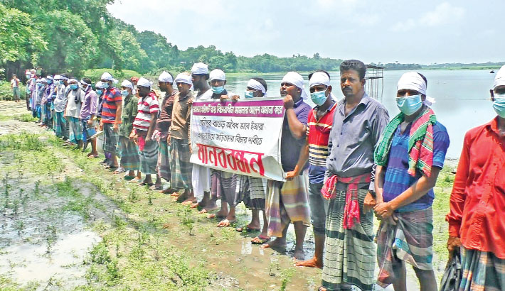 Fishermen form a human chain at Kusumpur village of Maheshpur upazila in Jhenaidah district on Saturday morning, demanding cancelation of illegal lease of Benipur Baor (water body).— Sun Photo