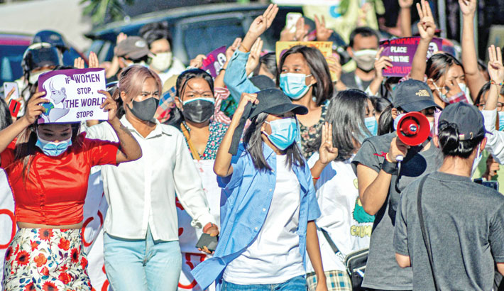 Women protesters make the three-finger salute as they take part in a demonstration against the Myanmar military coup in  Mandalay on Saturday. —AFP PHOTO