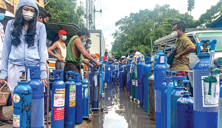 People stand with empty oxygen canisters as they wait to fill them up outside a factory in Yangon on Sunday, amid a surge in Covid-19 coronavirus cases. —AFP PHOTO