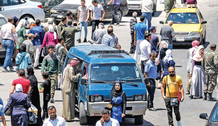 A man stands before a minibus for hire waiting along a road in Syria's capital Damascus on Monday.