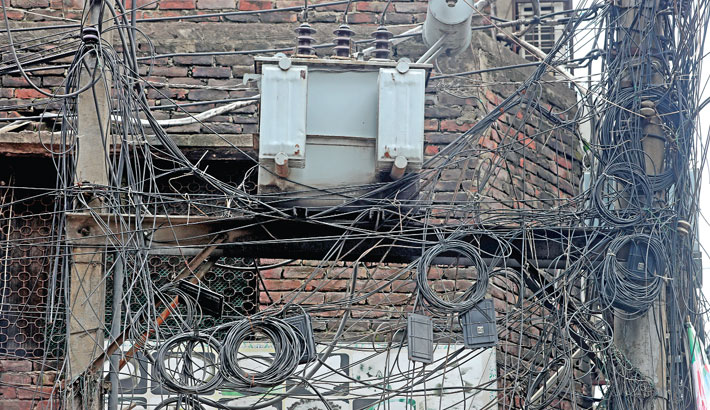 Internet and TV cables are hanging from electricity poles carrying high-voltage transformer in Old Dhaka's Bongshal area, posing risk of accidents. The photo was taken on Monday.—Reaz Ahmed Sumon