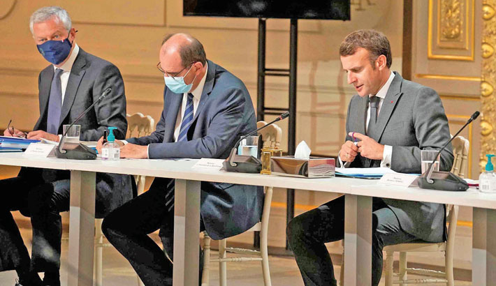 France's President Emmanuel Macron (R), flanked by France's Prime Minister Jean Castex (2ndL) and French Economy Minister Bruno Lemaire (L), meets French carmakers at the presidential Elysee Palace in Paris on Monday. Macron hosted a top-level virus security meeting in the morning and then will give a televised speech in the evening, the kind of solemn speech he's given at each turning point in France's virus epidemic.