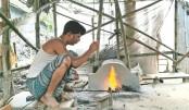 A blacksmith is making iron tools at Naldanga village in Jhenaidah district. Iron tools are now in high demand ahead of Eid-ul-Azha. The photo was taken on Monday.—Sun Photo